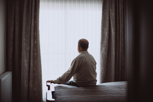 Growing old isn't for sissies. Shot of a depressed senior man sitting on his bed at home