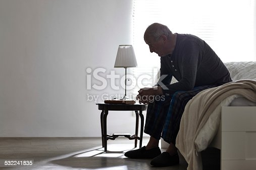 istock Elderly man sitting on bed looking serious 532241835