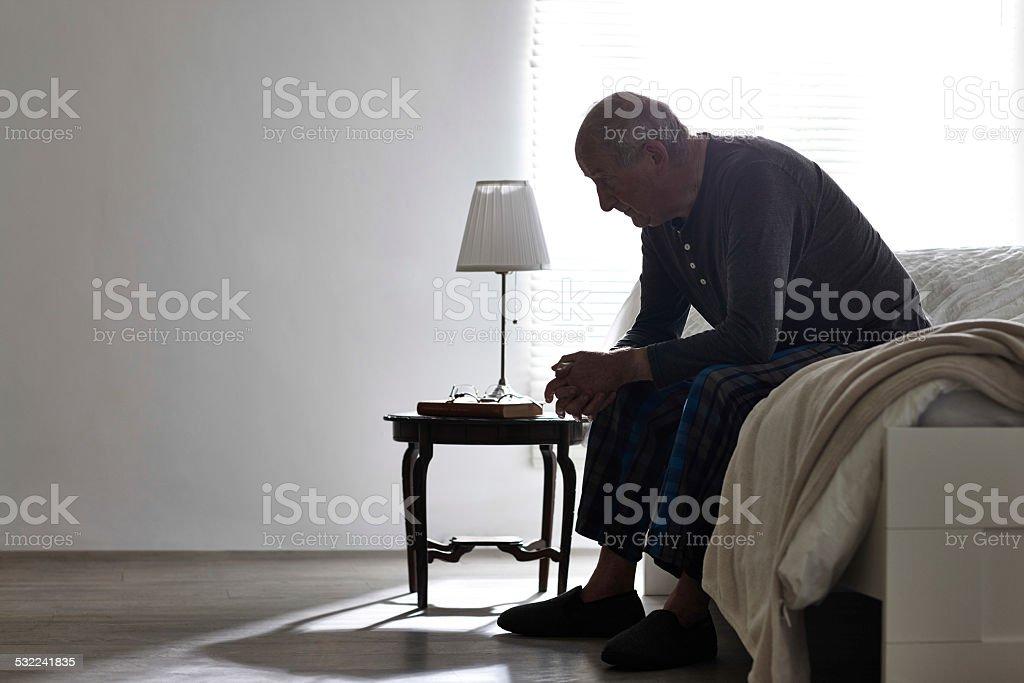 Älterer Mann sitzt auf dem Bett, die ernsthafte – Foto