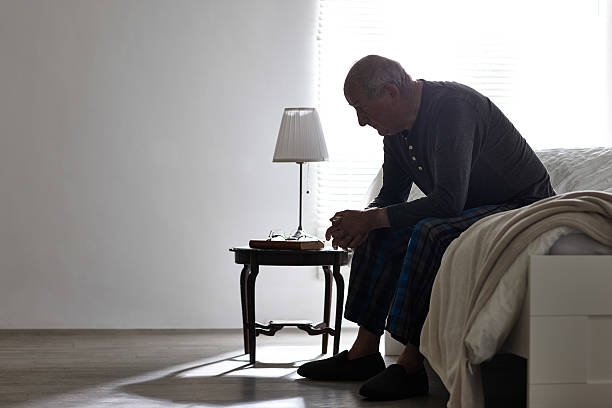 Elderly man sitting on bed looking serious Elderly man sitting on bed looking serious - Indoors desolation stock pictures, royalty-free photos & images