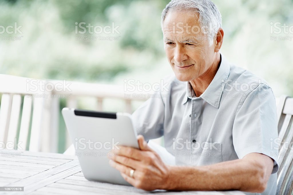 Elderly man sitting on bench while holding a tablet PC royalty-free stock photo