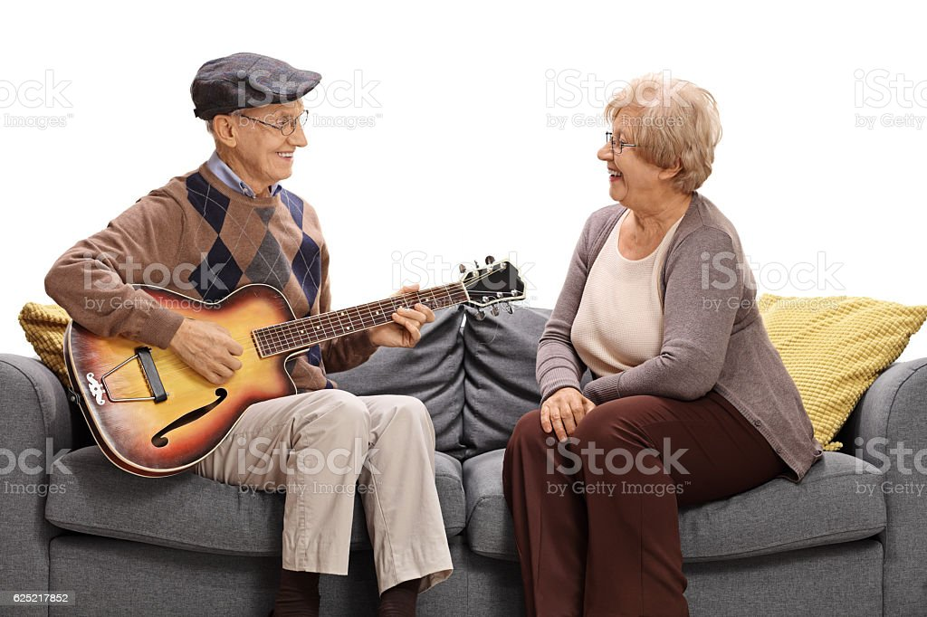 Elderly man sitting on sofa and playing guitar to woman stock photo