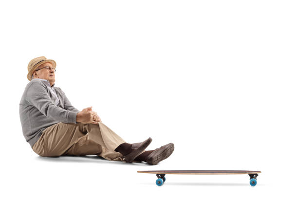 Elderly man sitting on the floor next to a longboard and holding his aching knee stock photo