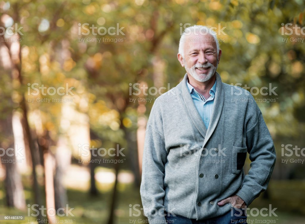 Elderly man smiling outdoors in nature stock photo
