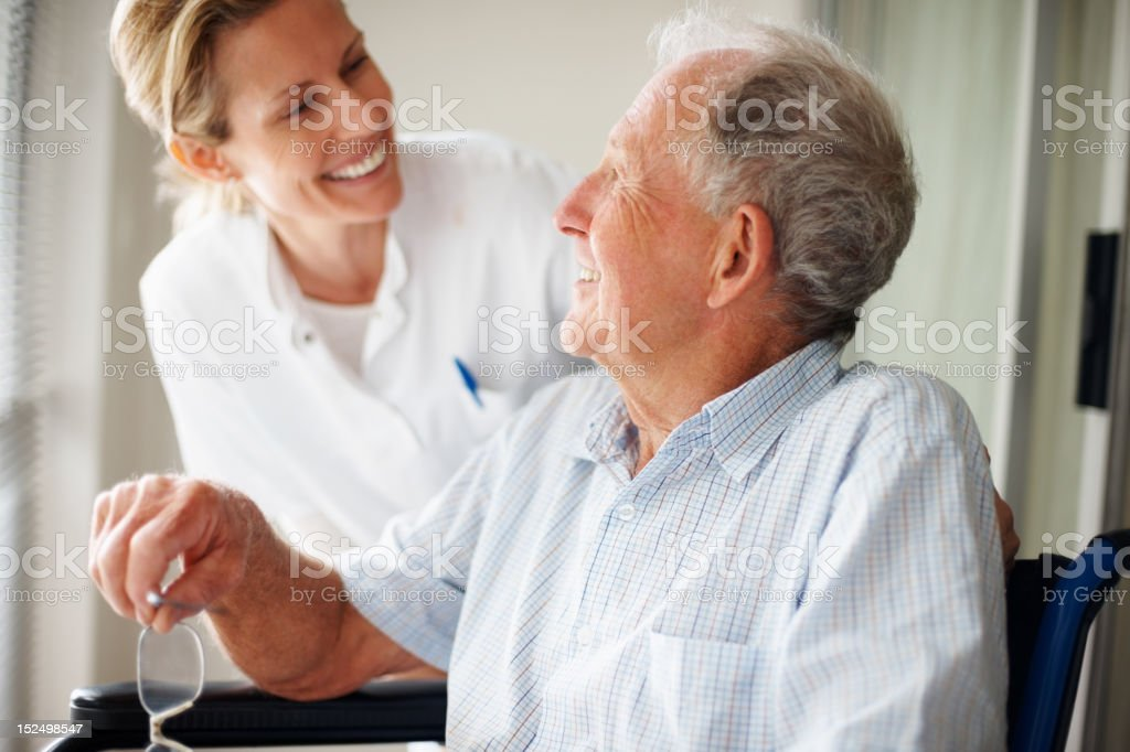 Elderly man speaking to a nurse stock photo