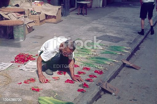 Hong Kong, China, 1974. Elderly man spreads his humble range of goods (vegetables) on a sidewalk.