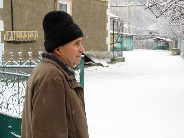 älterer mann stehend auf der ländlichen straße nahe dem eisernen tor und haus während eines schneefalls - eisenmangel was tun stock-fotos und bilder