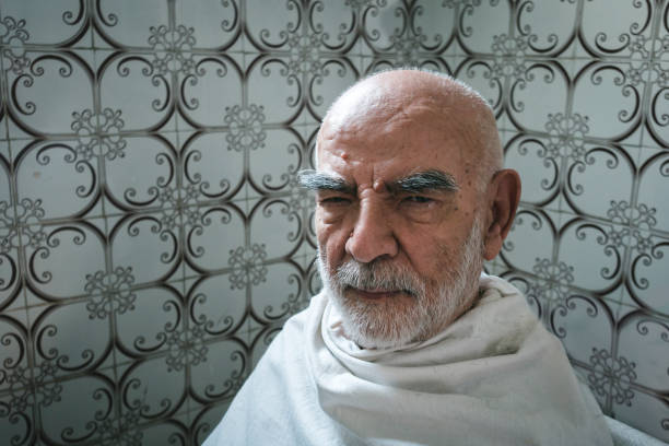 Elderly Man Staring at the Camera while waiting for His Haircut with white blanket on him. stock photo