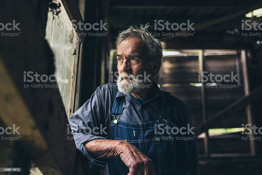 Elderly man staring out of a rustic wooden window stock photo