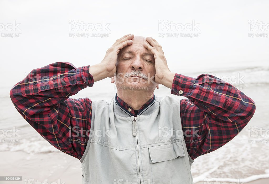 Elderly man suffering from a headache on sea background royalty-free stock photo
