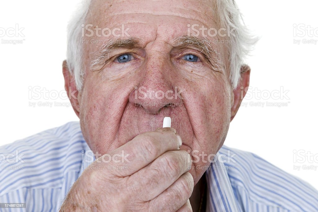 Elderly man taking a pill royalty-free stock photo