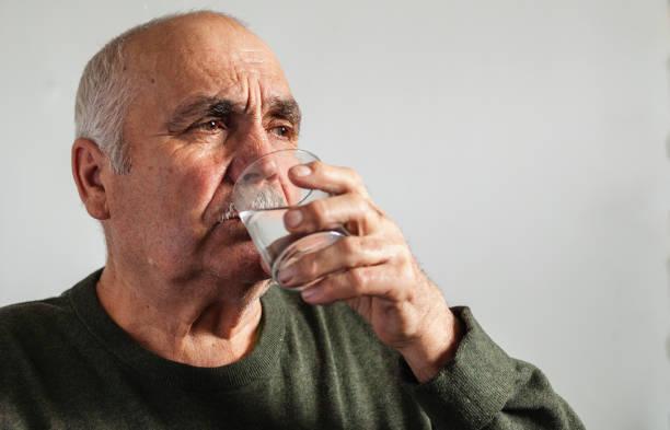 Elderly man taking medication with water stock photo