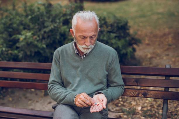 Elderly man taking prescription medicine in the park stock photo