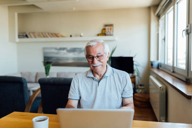 Elderly man using a laptop at home stock photo