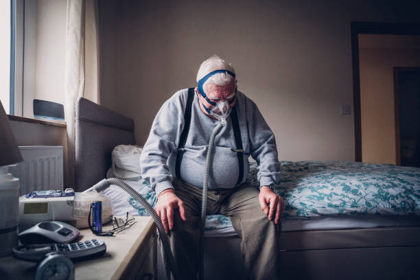 Elderly Man Using a Medical Breathing Apparatus stock photo