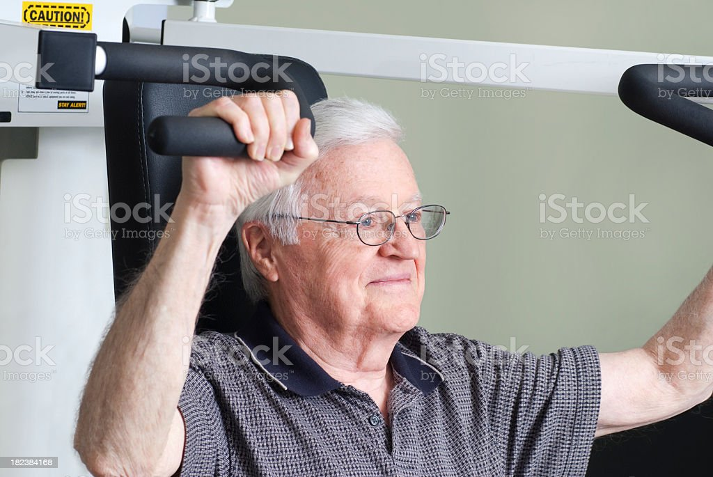 Elderly Man Using Arm Weight Machine Equiment royalty-free stock photo