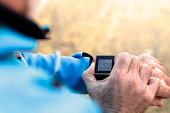 Elderly Man using Smart Watch measuring heart rate during walk