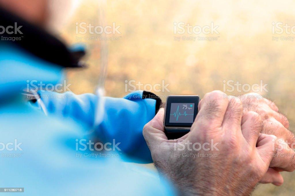 Elderly Man using Smart Watch measuring heart rate stock photo