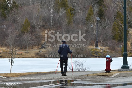 Saint John, New Brunswick / Canada - March 30 2019:  Elderly Man Using Trekking Poles Walking on a Path at Rockwood Park in the Early Spring