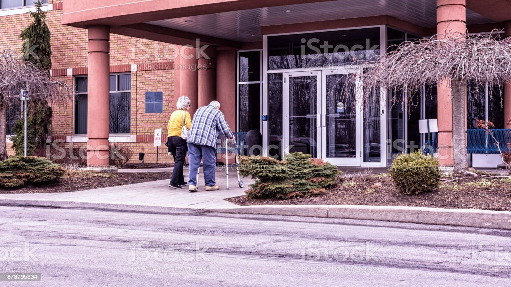 Elderly Man Using Walker Entering Medical Office With Daughter stock photo