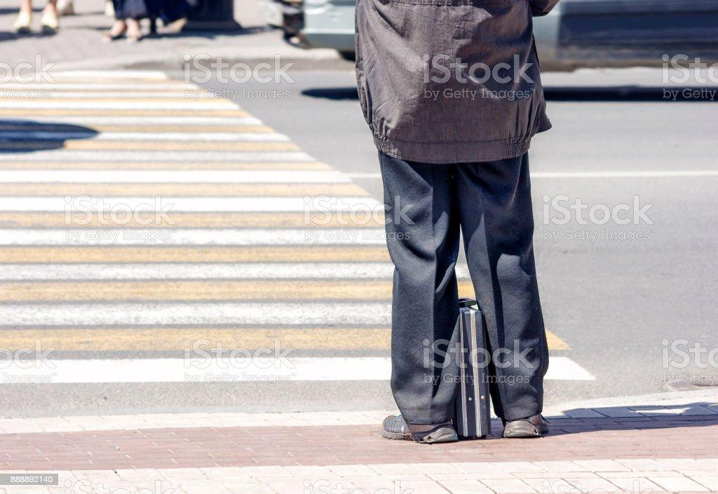 elderly man waiting to cross the street stock photo