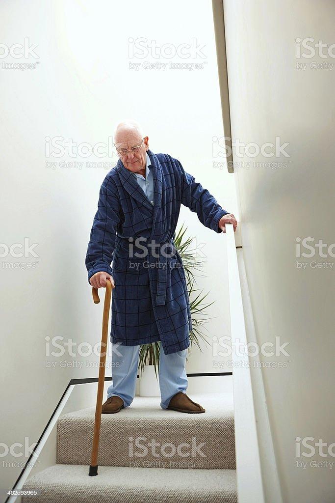 Elderly man walking down stairs royalty-free stock photo