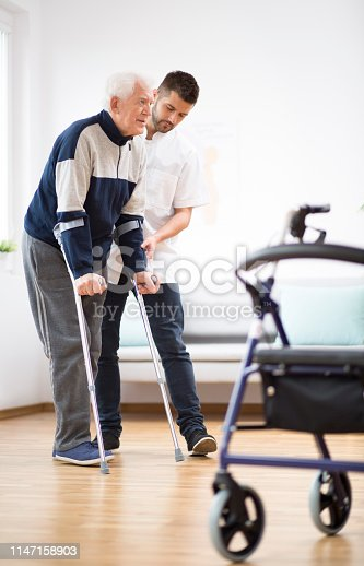 950649706istockphoto Elderly man walking on crutches and a helpful male nurse supporting him 1147158903
