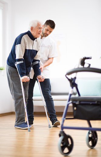 950649706 istock photo Elderly man walking on crutches and a helpful male nurse supporting him 1147158903