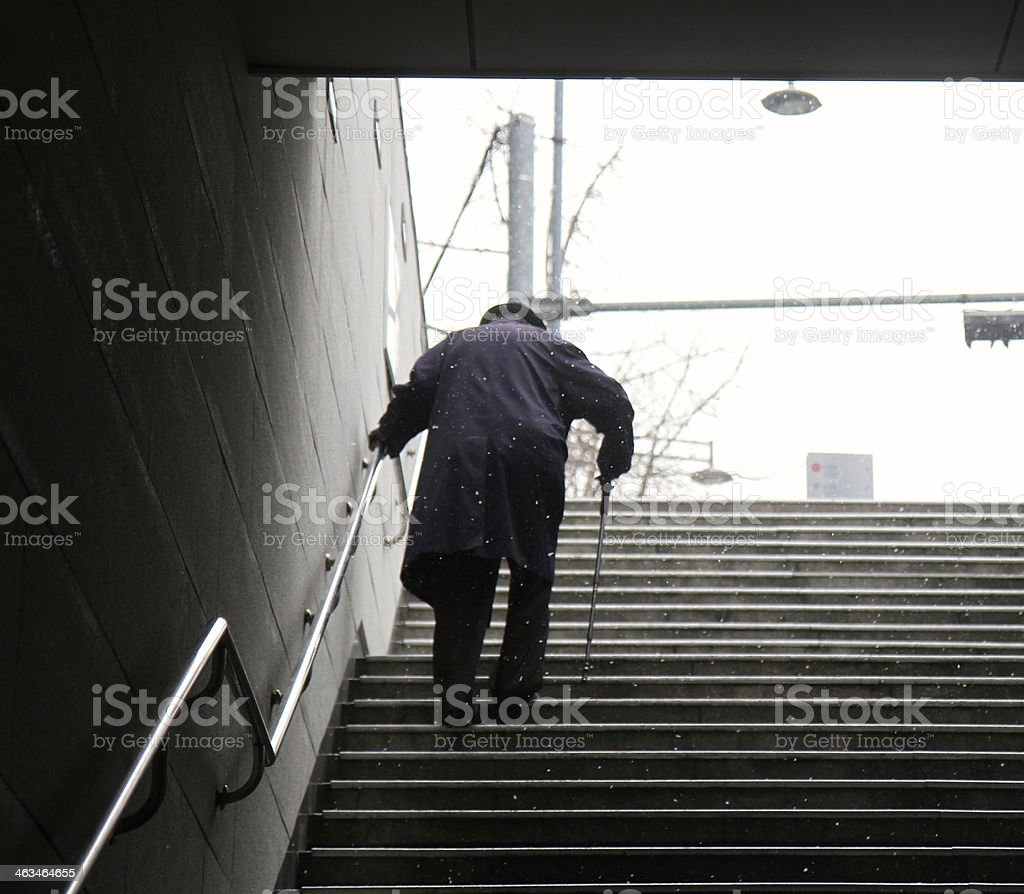 Elderly Man walking up a set of stairs during winter royalty-free stock photo