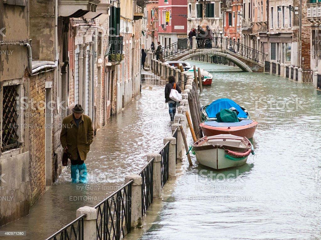 Elderly man walks along flooded embankment, Venice, Italy stock photo