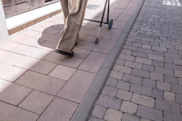 Älterer Mann geht über abgesenkten Bürgersteig mit Gehhilfe – Foto