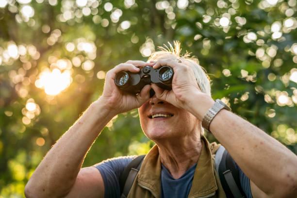 elderly man watching birds with binoculars - osservare gli uccelli foto e immagini stock