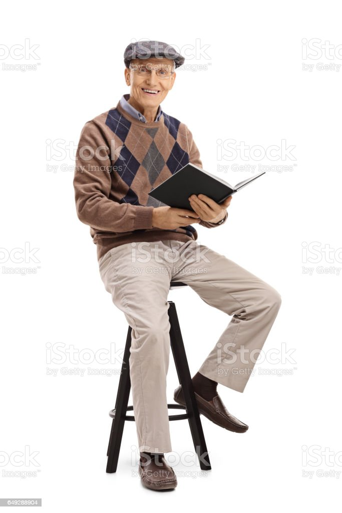 Elderly man with a book sitting on a chair stock photo