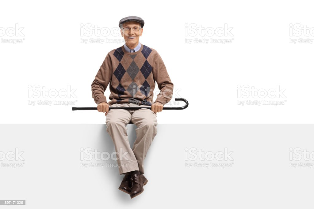 Elderly man with a cane seated on a panel stock photo