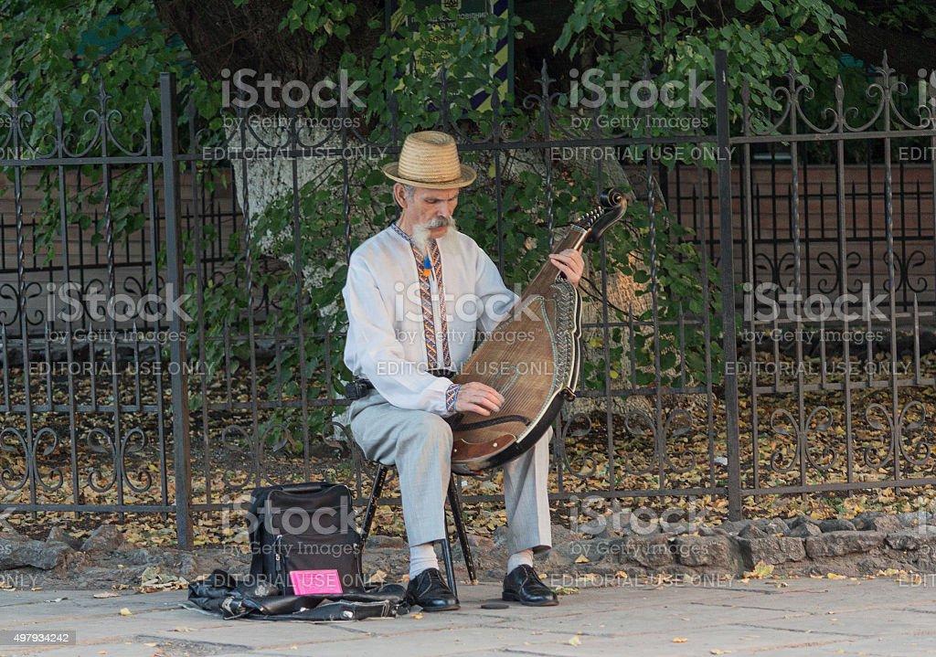 Пожилой мужчина с национальным колоритом играет на bandura стоковое фото