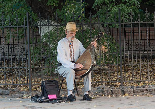 Cтоковое фото Пожилой мужчина с национальным колоритом играет на bandura