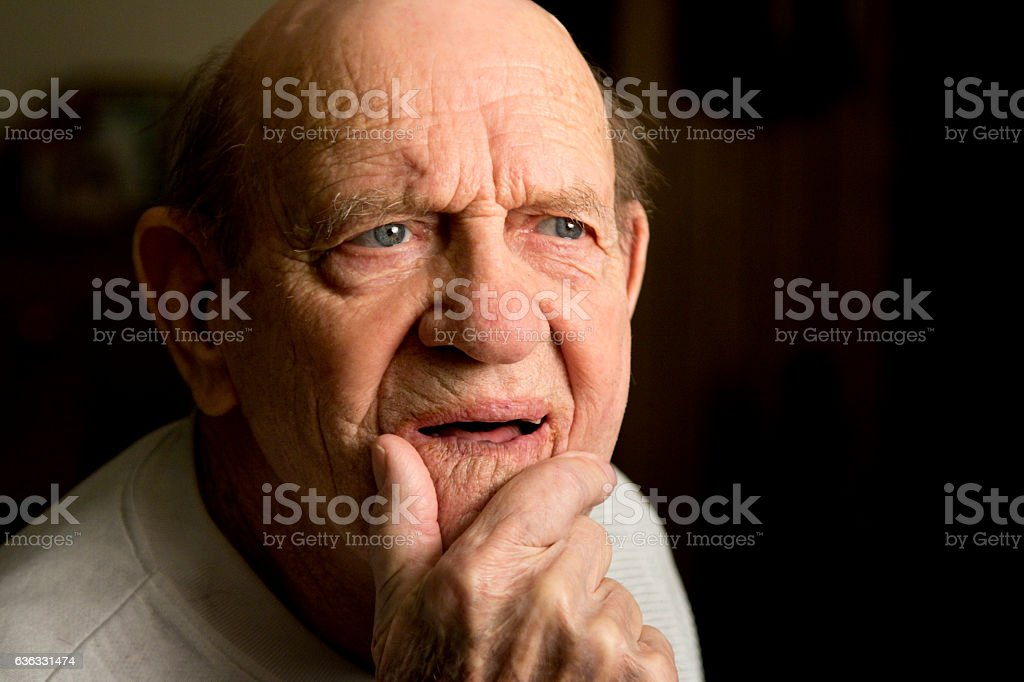 Elderly man with dementia and blank stare, hand on chin stock photo
