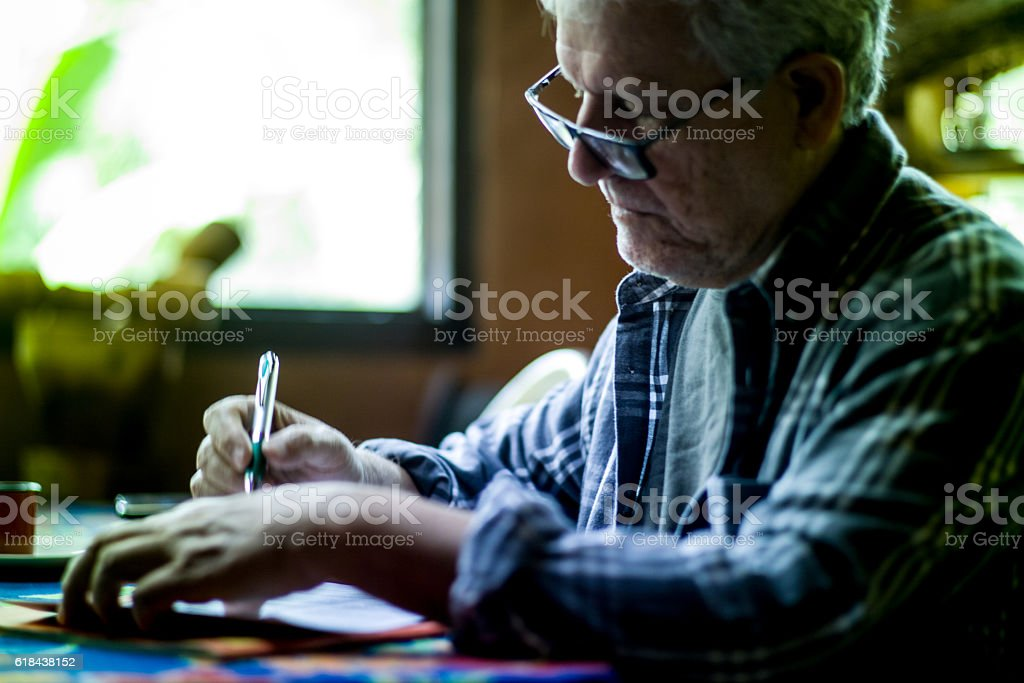 Elderly man with glasses signing a text on paper - foto de acervo