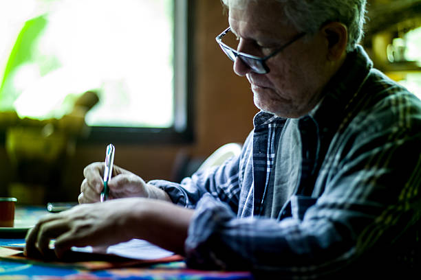 Elderly man with glasses signing a text on paper stock photo