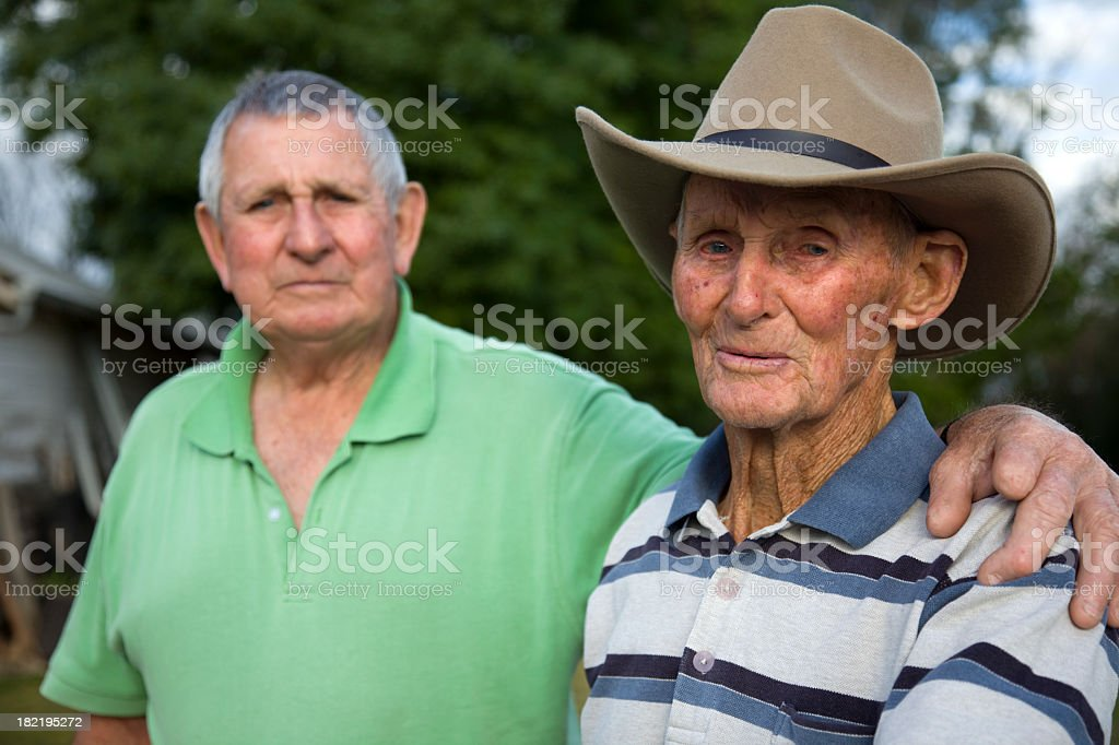 Elderly man with his arm around another elderly man stock photo