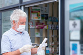 istock Elderly man with mask and protective gloves leaves the chemist's shop with medicines and instructions. Fear of coronavirus infection, covid-19. Concept of retired senior and fear of contagion 1214535480