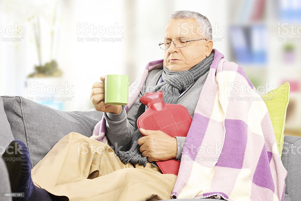 Elderly man with the flu warming up and drinking tea stock photo