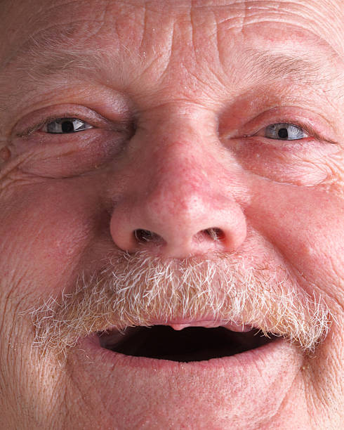 Elderly man with toothless smile stock photo