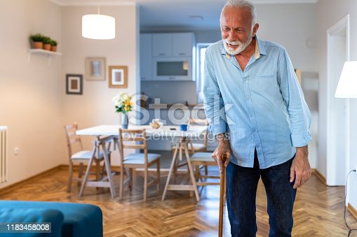 Senior Man on a rehabilitation after surgery or on recovery walks with walking cane at the home. Rehabilitation and healthcare concept.