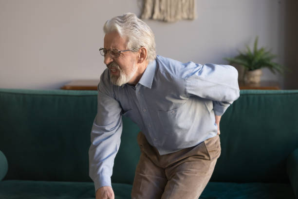 Elderly man writhes in pain suffers from low back strain Aged grey haired sixty years man in glasses writhes in pain suffers from low back strain, touch rubbing or massaging loin reduces backache. Degenerative disk disease, pinched nerve rheumatism concept dorsal surface stock pictures, royalty-free photos & images