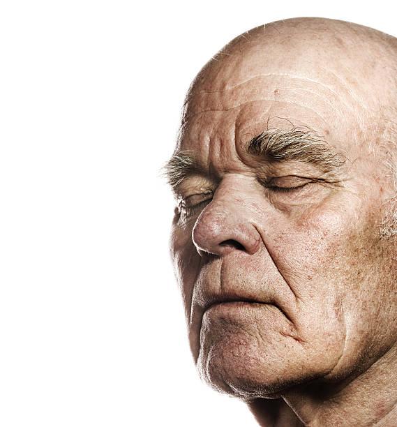 Elderly man's face over white background stock photo