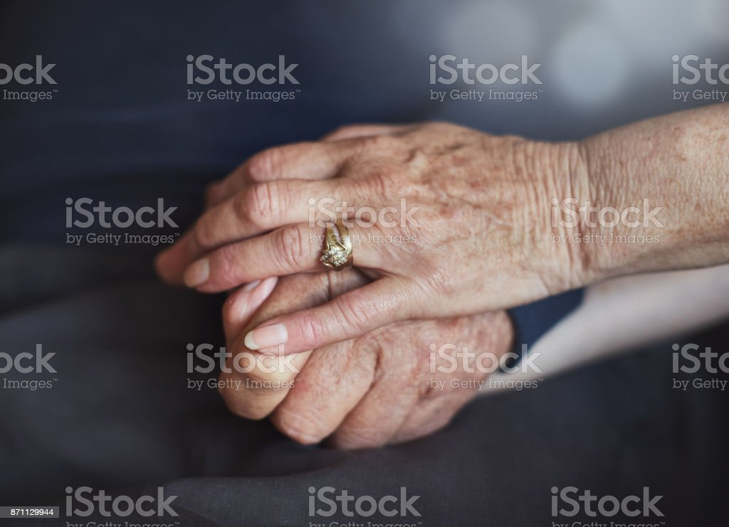 Elderly married couple's hands; she pats his reassuringly stock photo