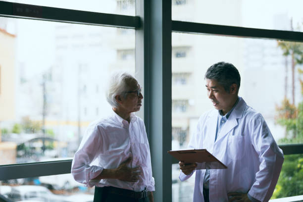 高齢者男性と中年男性の医師の医療記録について話しています。 ストックフォト
