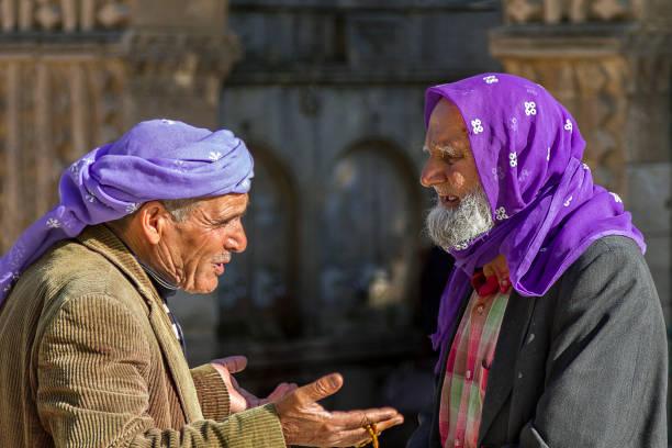 sanliurfa, türkei - 11. april 2014: ältere männer in lokalen lila kopfschmuck miteinander reden in sanliurfa, türkei. - kurdische sprache stock-fotos und bilder