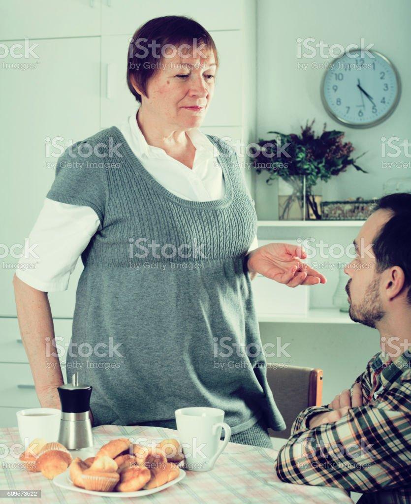 Elderly mother teaches her son stock photo